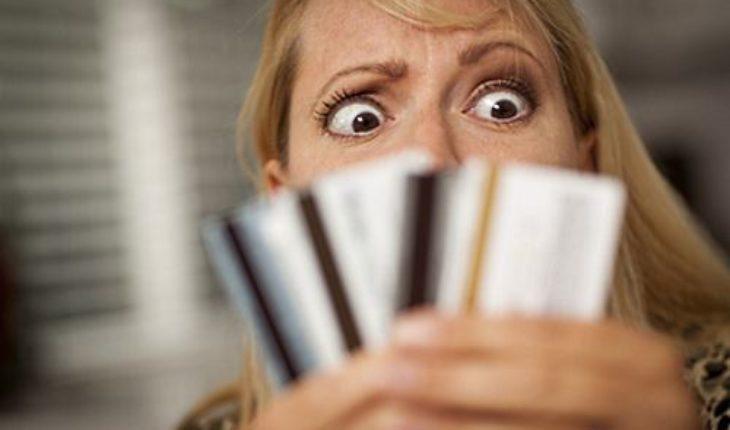 Credit Card Debt: Upset Woman Glaring At Her Many Credit Cards.