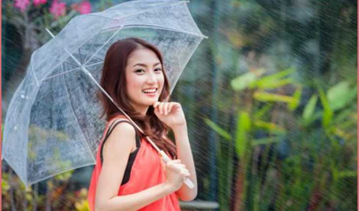 young Thai lady standing with under umbrella under rainning